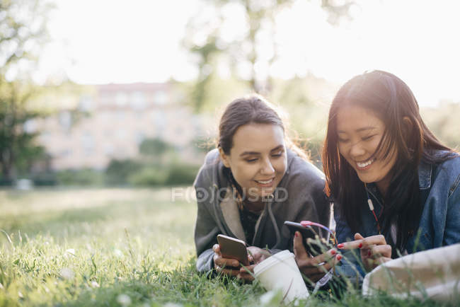 Smiling female friends using smart phones while lying on grass — Foto stock