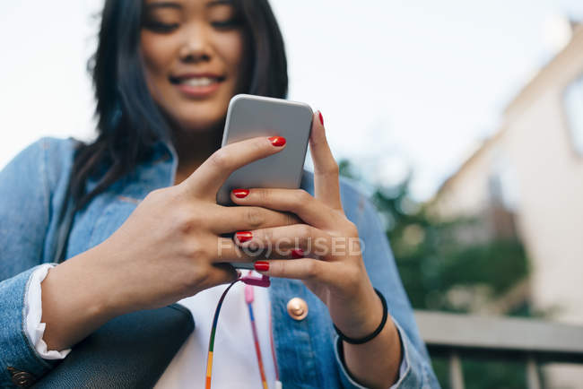 Visão de baixo ângulo de sorrir adolescente segurando telefone inteligente — Fotografia de Stock