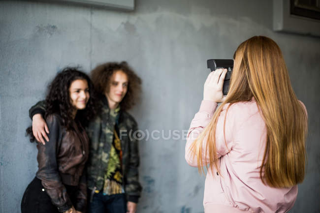Rear view of girl photographing teenage friends standing against wall at parking garage — Stock Photo