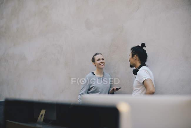 Programmatore di computer sorridente che tiene lo smart phone mentre discute con un collega maschio contro il muro in ufficio — Foto stock
