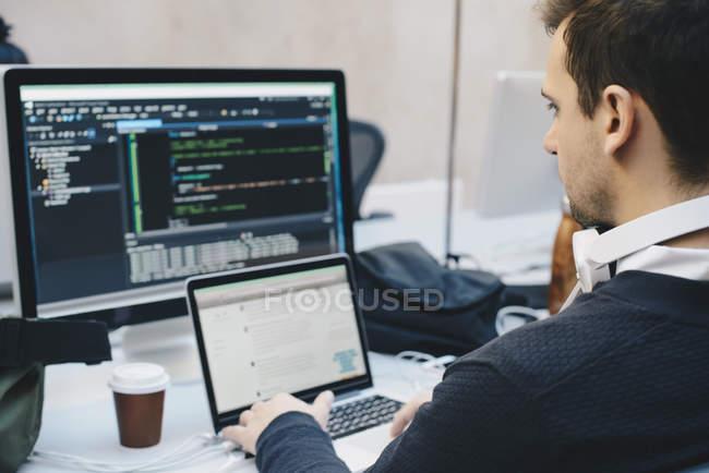 Sur la vue de l'épaule de l'homme d'affaires de programmation sur les ordinateurs au bureau créatif — Photo de stock