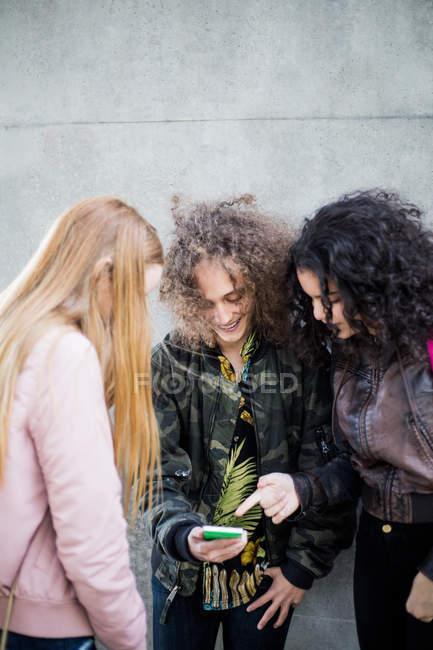 Усміхаючись підлітком, показуючи смарт-телефон друзям стіни — стокове фото