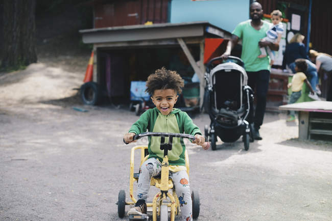 Happy boy riding tricycle while father and brother walking in background — Stock Photo