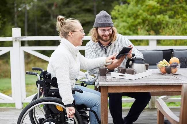 Young male caretaker and disabled woman using digital tablet in yard — стоковое фото