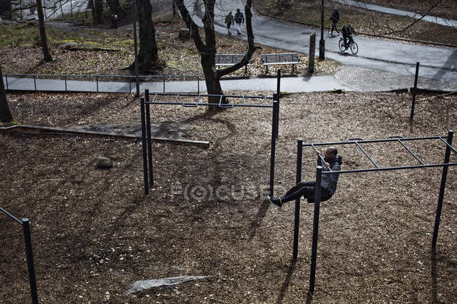 High angle view of male athlete hanging from monkey bars in forest — Stock Photo