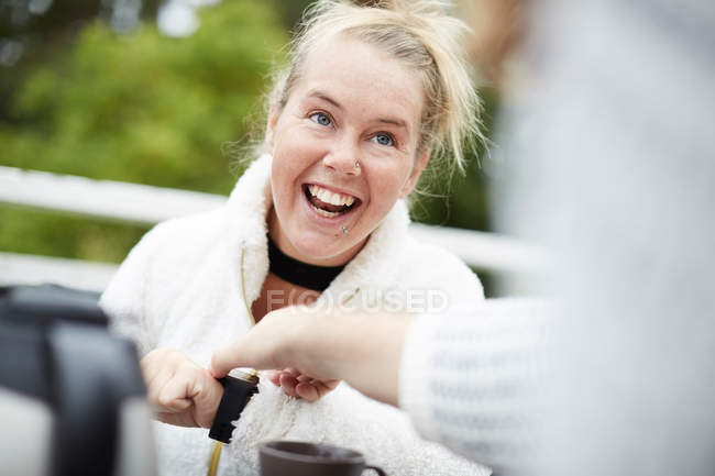Cropped image of male caretaker adjusting time on wristwatch of disabled woman in backyard — Stock Photo