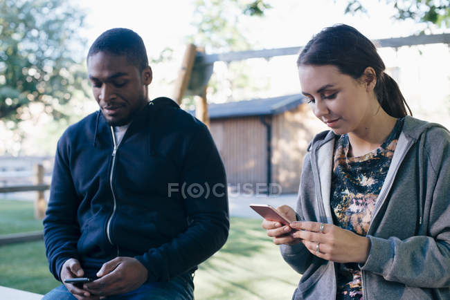 Jovens amigos multi-étnicos usando telefones inteligentes — Fotografia de Stock