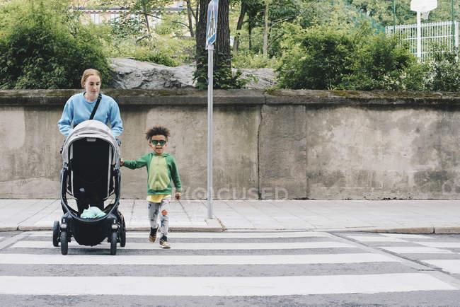 Mãe empurrando carrinho de bebê ao cruzar a estrada com o filho na cidade — Fotografia de Stock
