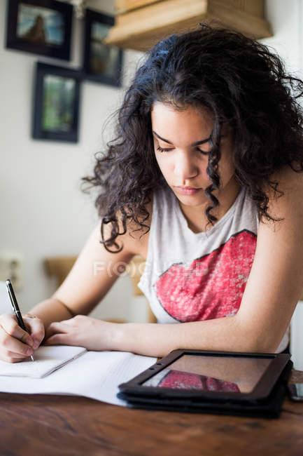 Дівчинка-підліток навчання в таблиці під час написання книги, цифровий планшетний — стокове фото