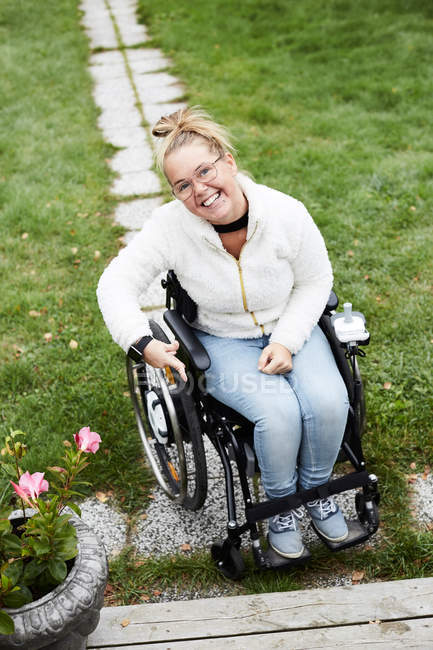Full length portrait of smiling disabled woman sitting on wheelchair in backyard — Stock Photo