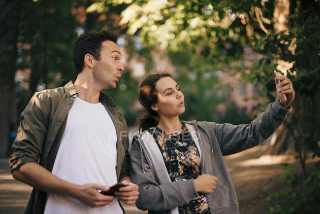 Donna allegra scattare selfie con amico maschio da smart phone — Foto stock