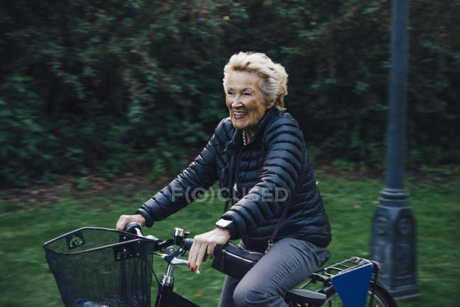 Smiling senior woman riding bicycle in park — Stock Photo