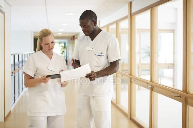 Enfermeiras masculinas e femininas usando tablet digital enquanto examinam documento no corredor hospitalar — Fotografia de Stock