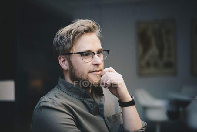 Pensiero programmatore di computer maschile con mano sul mento guardando lontano in ufficio — Foto stock