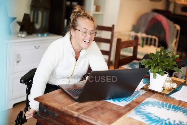 Улыбаясь отключены женщина, используя ноутбук столом в доме — стоковое фото