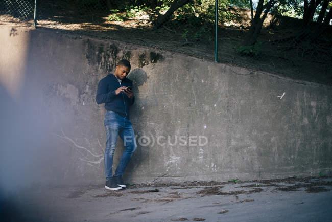Longitud completa de hombre joven apoyado en la pared mientras se utiliza el teléfono inteligente - foto de stock