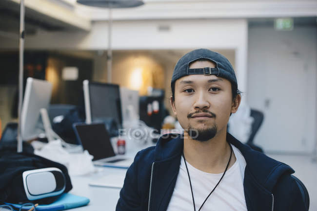 Portrait of confident computer programmer wearing cap in office — Stock Photo