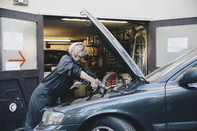 Side view of female mechanic repairing car outside auto repair shop — Stock Photo