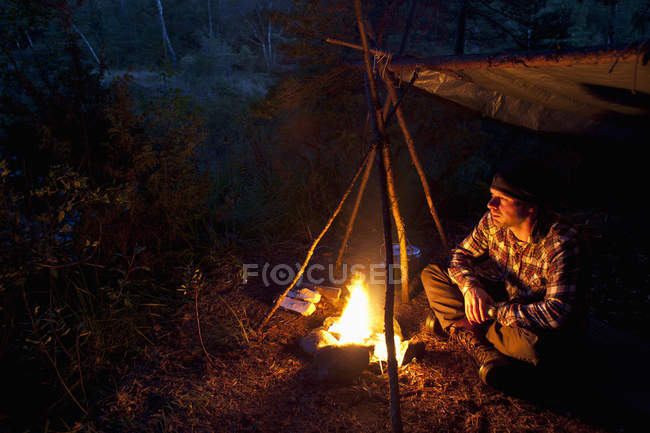 Man sitting by bonfire in forest at night — Stock Photo