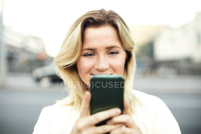 Young woman using mobile phone in city — Stock Photo