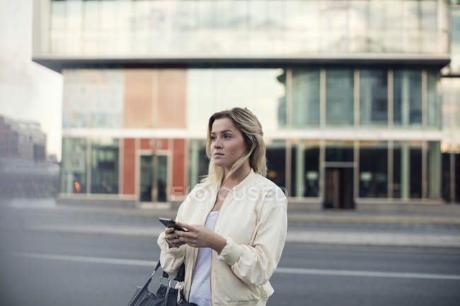 Young woman with mobile phone walking in city — Stock Photo