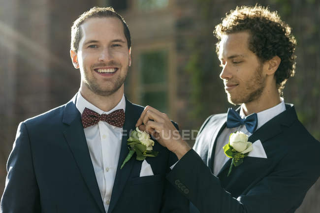 Portrait of happy man standing with gay partner adjusting boutonniere — Stock Photo