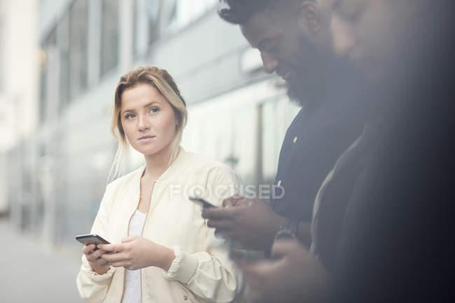 Jovem mulher olhando para amigos usando telefones inteligentes na cidade — Fotografia de Stock