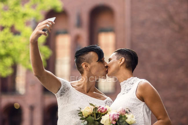 Lesbian couple taking selfie from mobile phone while kissing — Stock Photo
