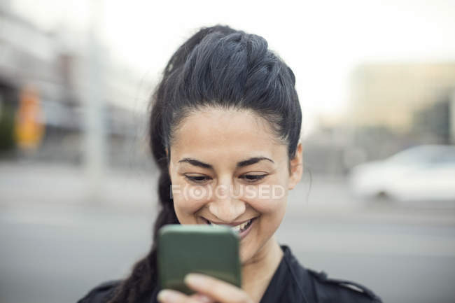 Happy young woman using smart phone in city — Stock Photo