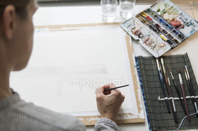 High angle view of female hand with brush and watercolors — Stock Photo
