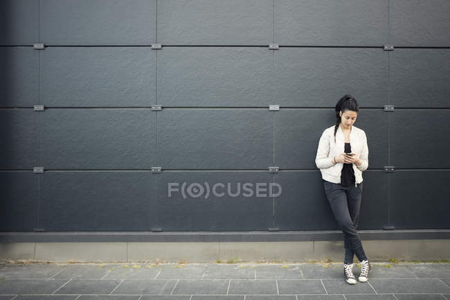 Young woman using smart phone against black wall — Stock Photo
