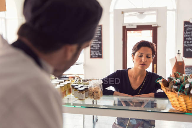 Woman buying grocery from male owner at store — Stock Photo