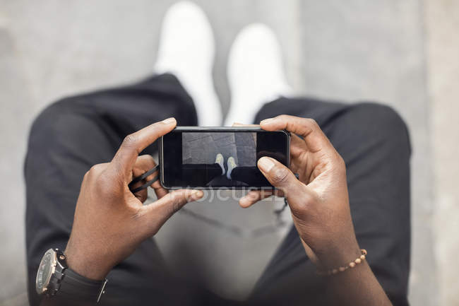 Vue d'angle élevé des mains mâles à l'aide de smartphone — Photo de stock