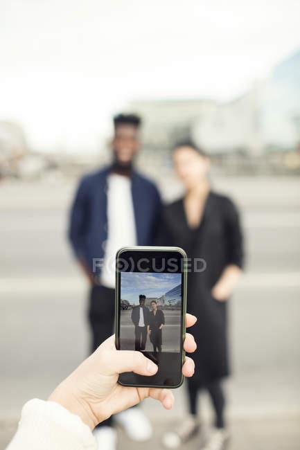 Cortada a imagem da mulher fotografando amigos na cidade — Fotografia de Stock