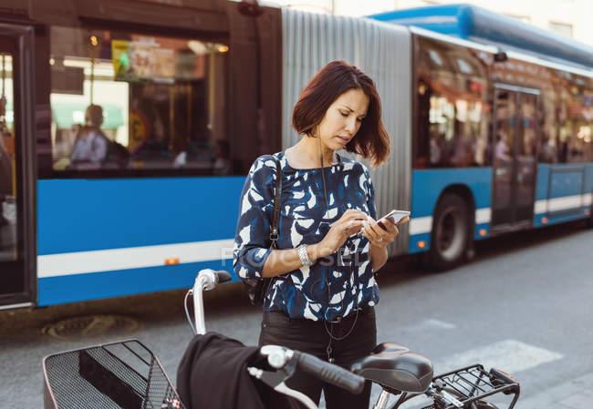 Femme d'affaires utilisant un téléphone intelligent tout en se tenant debout avec vélo sur la rue de la ville — Photo de stock