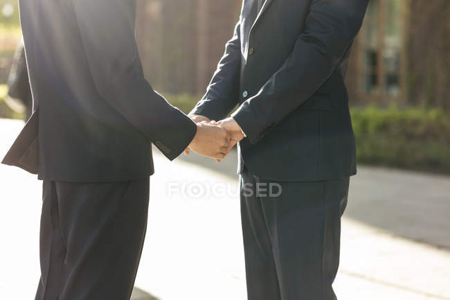 Midsection of newlywed gay couple holding hands — Stock Photo