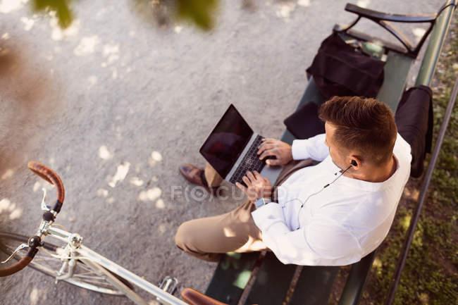 Vista de alto ângulo do homem de negócios usando laptop enquanto sentado no banco do parque — Fotografia de Stock