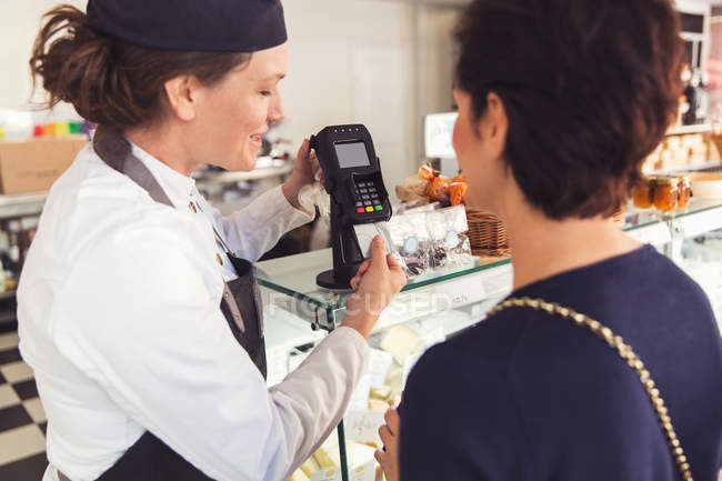 Saleswoman assisting female customer with credit card reader at grocery store — Stock Photo