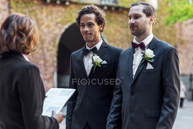 Couple gay debout devant le prêtre aîné lors de la cérémonie de mariage — Photo de stock