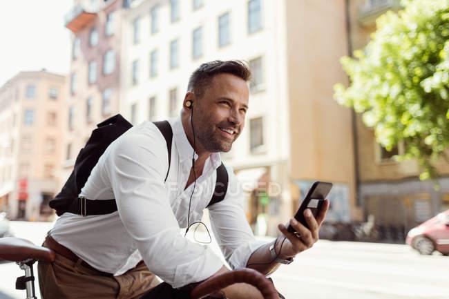 Empresário sorrindo olhando para longe enquanto segurava o telefone inteligente na rua — Fotografia de Stock