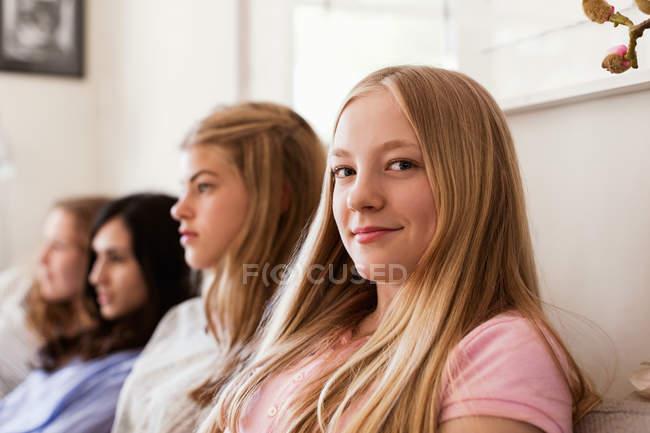 Портрет уверенной девочки-подростка, сидящей на диване, в то время как друзья смотрят телевизор дома — стоковое фото