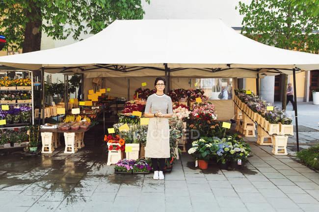 Portrait of female owner standing outside flower shop — Stock Photo