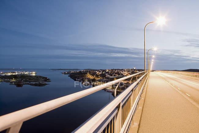 Illuminated bridge over calm sea and city lights against sky at dusk — Stock Photo