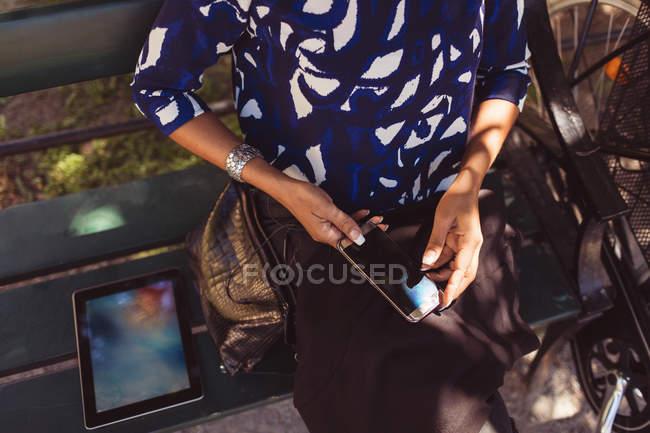 Высокий угол животик бизнесвумен, используя смарт-телефона, сидя на скамейке в парке — стоковое фото