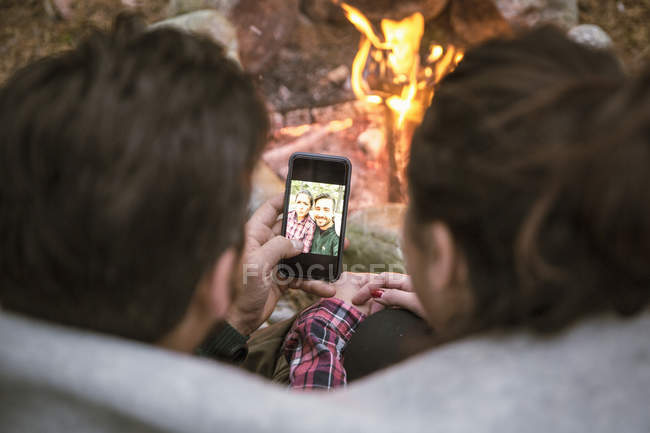 High angle view of couple taking selfie in mobile phone by fire pit at campsite — Stock Photo