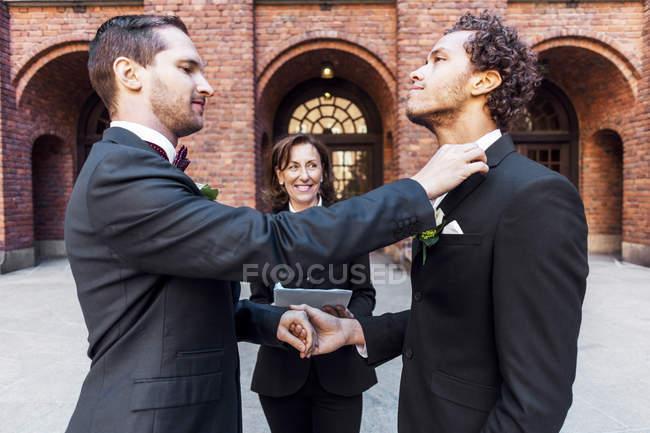 Homme ajustant noeud papillon de partenaire gay devant prêtre lors de la cérémonie de mariage — Photo de stock