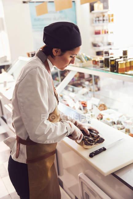 Vista laterale del proprietario taglio della carne al bancone in negozio di alimentari — Foto stock