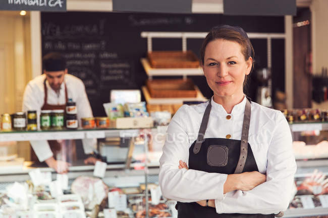 Portrait of confident owner standing arms crossed while colleague working in background at grocery store — Stock Photo