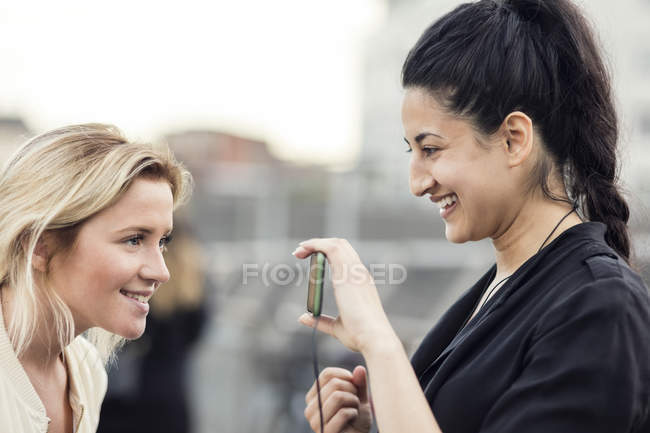 Side view of happy woman showing mobile phone to friend — Stock Photo