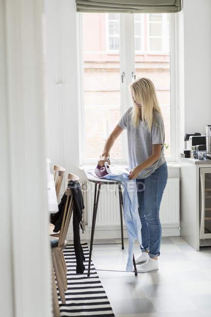 Chica adolescente planchando ropa contra la ventana en casa - foto de stock